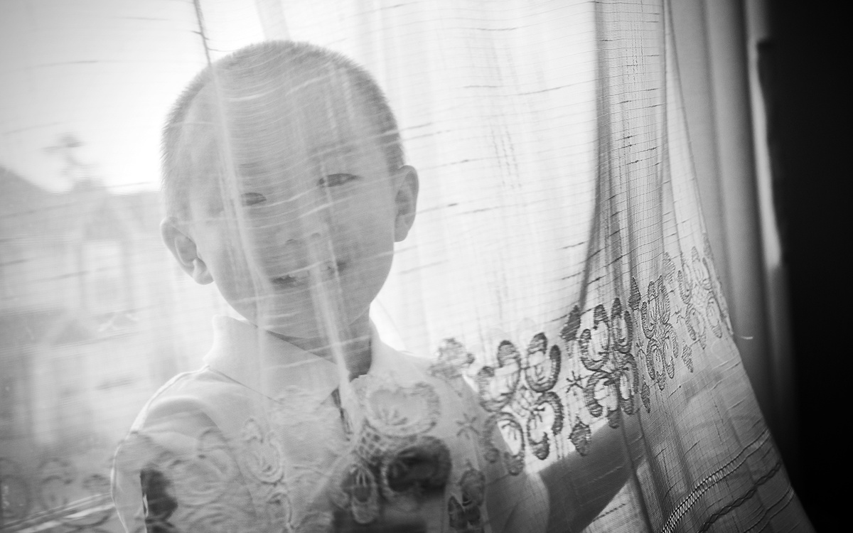 A boy poses behind a curtain in chapel hill, nc