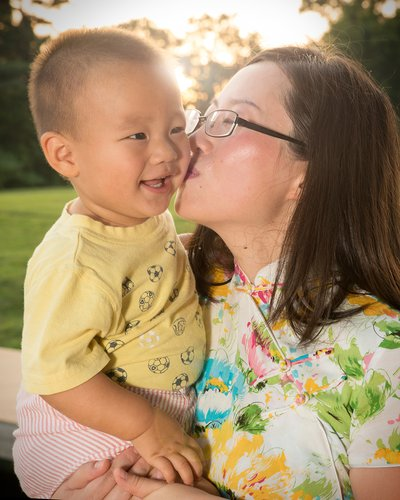 a mom kisses her baby at a family portrait session at Lake Hogan Farms in Chapel Hill, NC