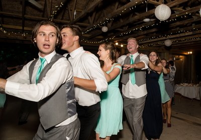 Guests form a conga line at a wedding reception at Carrigan Farms in Charlotte, NC
