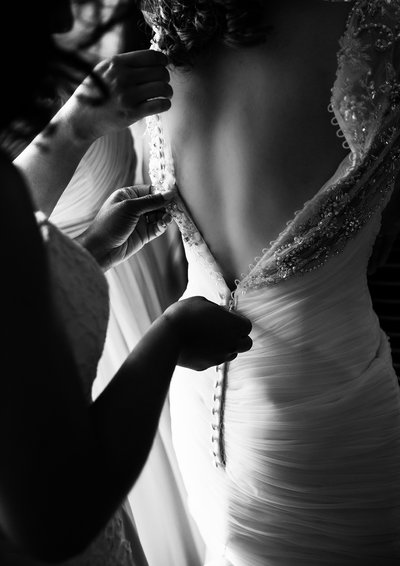 A bride is zipped into her wedding dress before a wedding at All Saints Chapel in Raleigh, NC