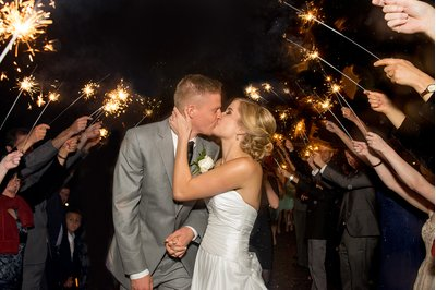 A bride and groom kiss in front of sparklers at a wedding at Carrigan Farms in Charlotte, NC