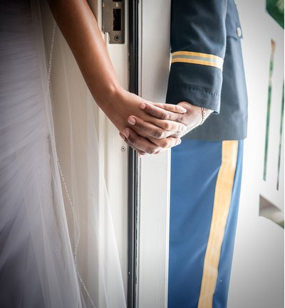 a bride and groom hold hands around a door before a wedding at all saints chapel in raleigh, nc