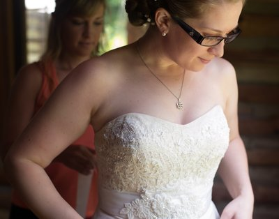 A bride dresses before a wedding at the Spruce Pine Lodge in Bahama, NC
