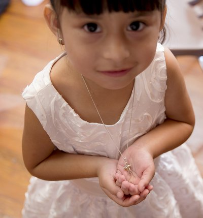 a flower girl shows off her favorite necklace at a wedding at spruce pine lodge in bahama, nc