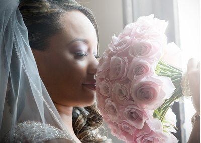 A bride with a pink rose bouquet at a wedding at All Saints Chapel in Raleigh, NC