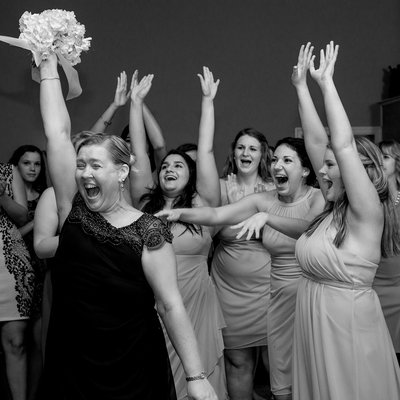 The mother of the bride catches the bouquet at a wedding reception at Asbury Park Grove in Charlotte, NC