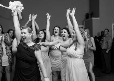 The mother of the bride is thrilled after catching the bouquet at a wedding in charlotte, nc