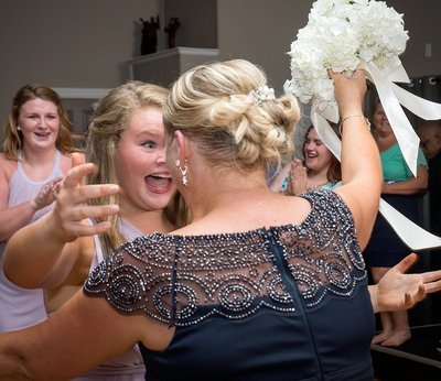 A daughter hugs her mother after she catches the bouquet at a wedding in Charlotte, NC