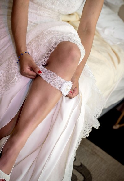 a bride puts on her garter belt before a wedding in the blue ridge mountains