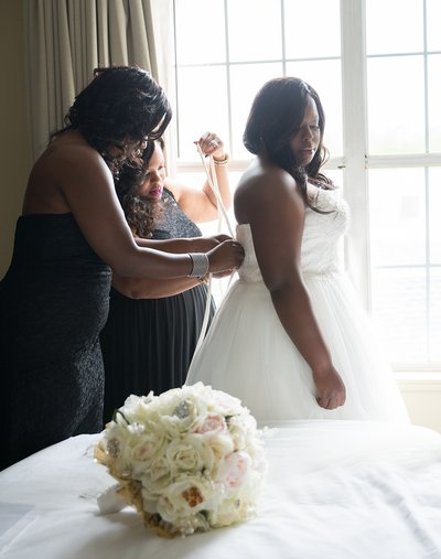 Brides maids help a bride dress at a wedding at the DoubleTree Suites in Durham, NC