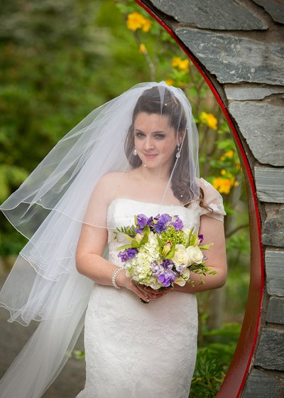 A bride poses with her bouquet at the UNC Charlotte Botanical gardens