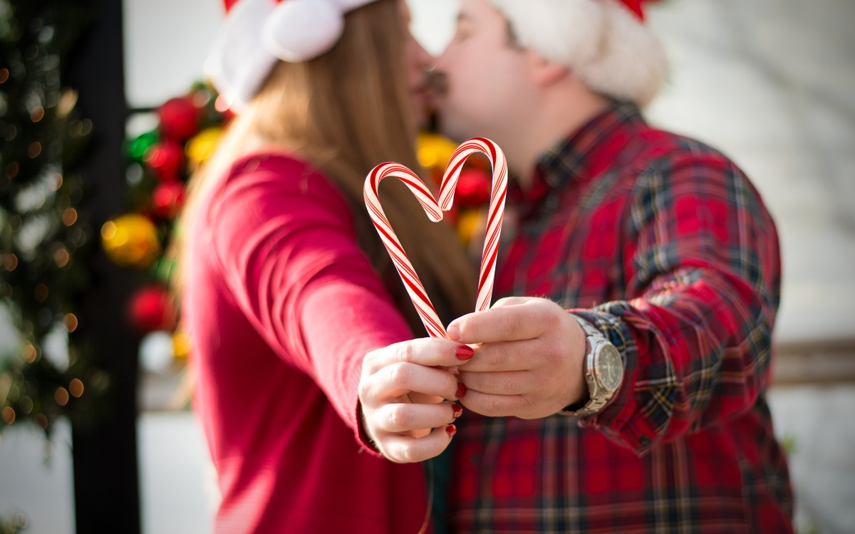 An engaged couple pose for a holiday photo in raleigh, nc