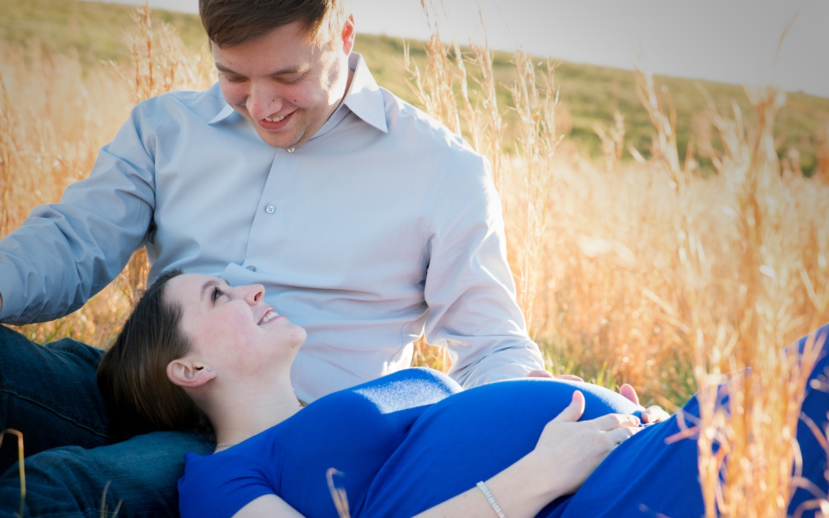 A pregnant couple poses in a wheat field in Charlotte, nc
