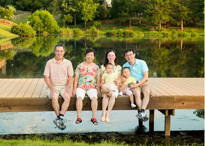 A family poses on the dock at a family portrait session at Lake Hogan Farms in Chapel Hill, NC