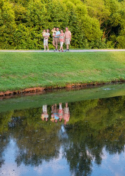 A family poses in front of a lake at a family portrait session at Lake Hogan Farms in Chapel Hill, NC