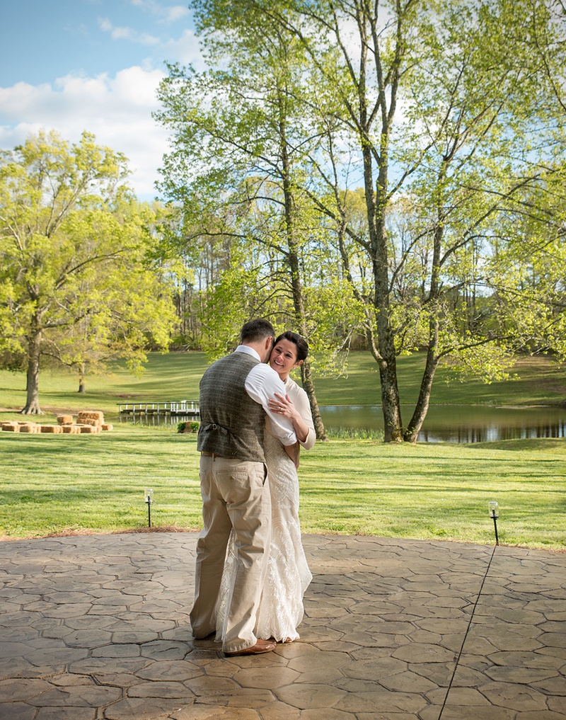 A bride and groom's first dance in front of the lake at the cabin at hillside farms in henderson, nc