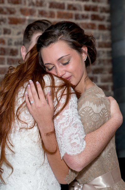 A brides maid hugs a bride after a toast at a wedding at the stockroom at 230 in raleigh, nc