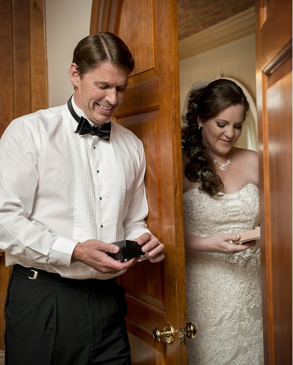 Bride and Groom exchange gifts behind a door at a wedding at Matthews House in Cary, NC