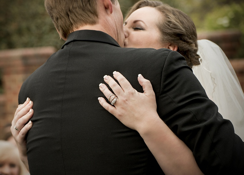Bride and Groom kiss at a wedding ceremony at Matthews House in Cary, NC