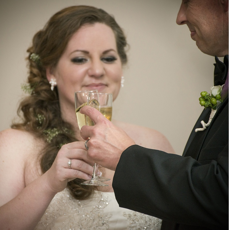 A bride and groom toast at a wedding reception at Matthews House in Cary, NC