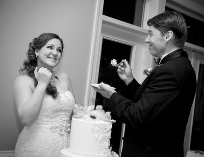 A bride and groom cut the cake at a wedding reception at Matthews House in Cary, NC