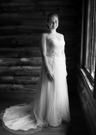 A bride poses by a window at a wedding at Spruce Pine Lodge in Bahama, NC