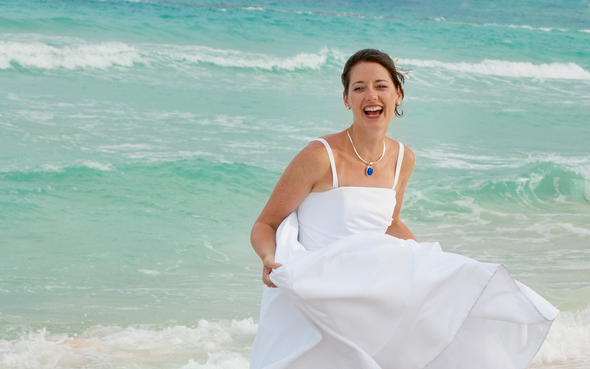 A bride splashes in the ocean at a beach wedding in North Carolina