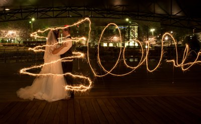 A couple embrace with sparkler writing at a wedding in Raleigh, NC
