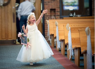 A flower girl at a wedding ceremony waves in Raleigh, NC