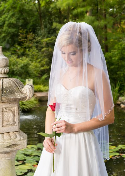 A bride poses with a red rose at the unc botanical gardens in charlotte, nc