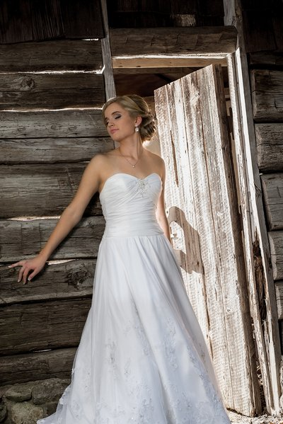 A bride poses in front of a cabin at the UNC Charlotte Botanical gardens