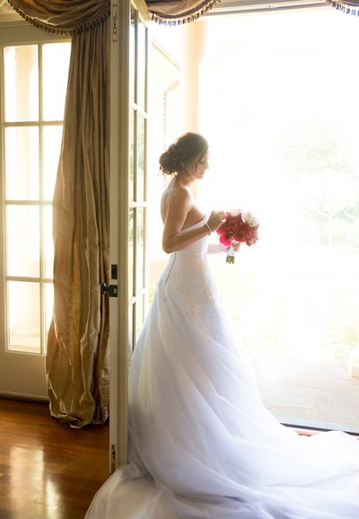 bride standing in an open door with a red bouquet