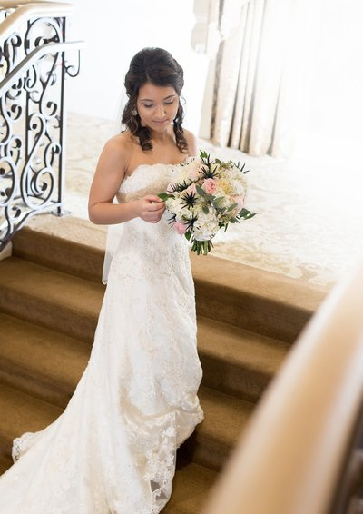 A bride posses with her bouquet on the stairs