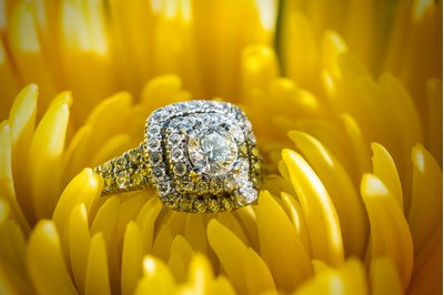 An engagement ring on a yellow flower