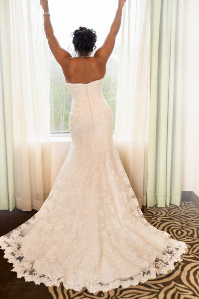 A bride poses in front of a window at the Hilton Garden Inn in Raleigh, NC