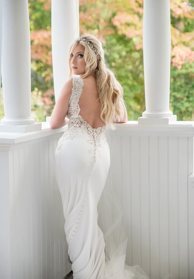 A bride posts in front of white columns