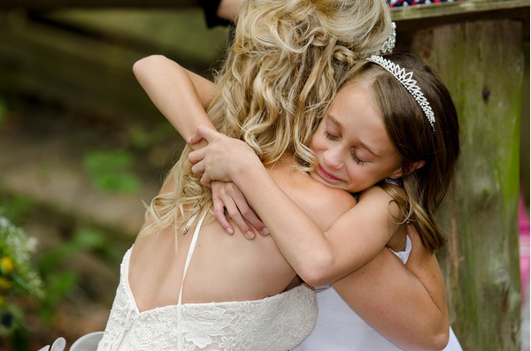 A bride hugging her flower girl at a wedding in the Clemmons Educational State Forest