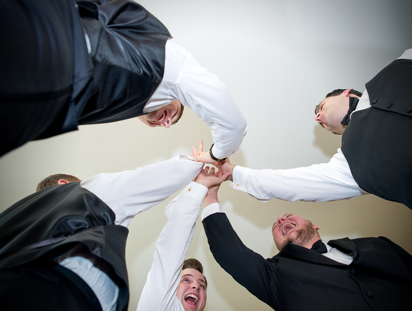 A groom and his groomsmen give a high five fist bump at a wedding at the stockroom at 230 in raleigh, nc