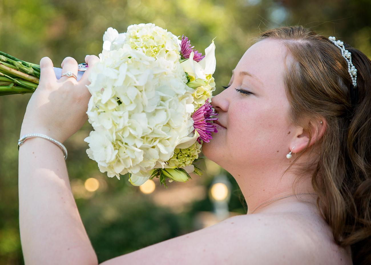 A bride enjoys her fragrant bouquet at a Tuscany Garden Wedding in Greensboro, NC