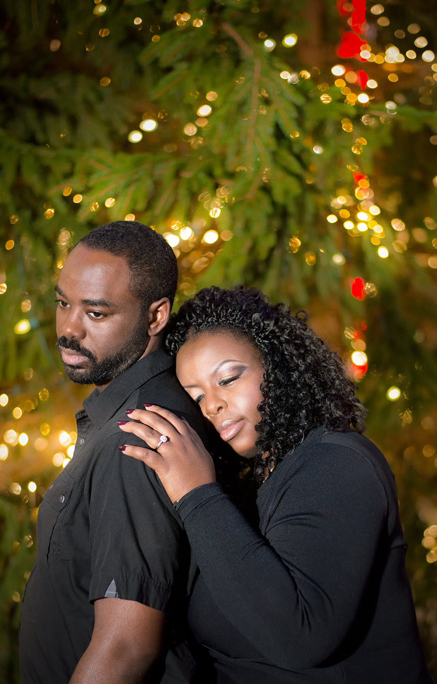 A couple pose in front of a Christmas tree in downtown Raleigh, NC
