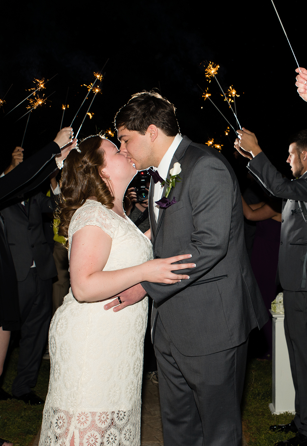 A couple kiss in front of sparklers at a Tuscany Garden wedding in Greensboro, NC