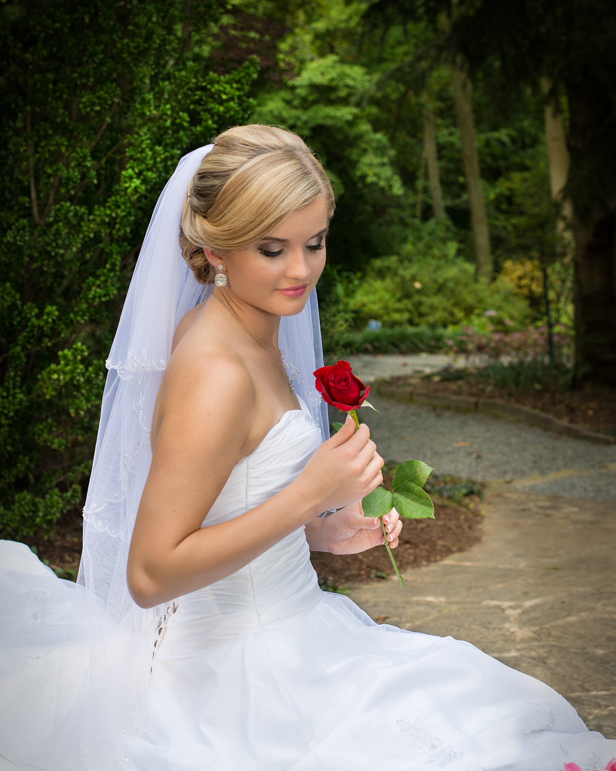 A bride poses with a red rose at the UNC Charlotte Botanical gardens